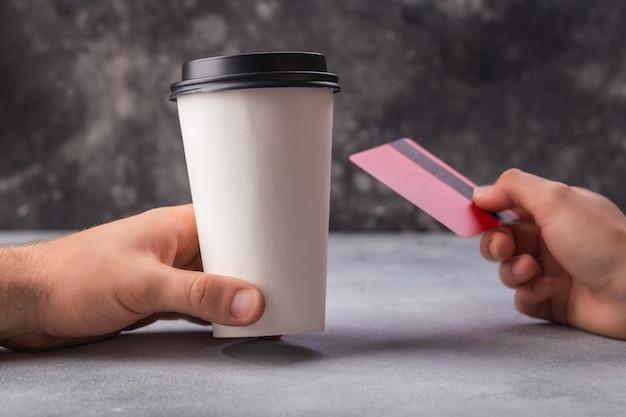 Оплата за кофе в белой чашке красными кредитками женских и мужских рук