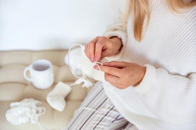 ブロンドの女の子がウールからベビーソックスを編む