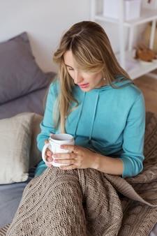 青いスウェットシャツの女の子がウールの毛布に包まれて熱いお茶を飲む