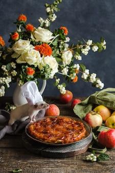 クリスマスの組成物。ネズミはアップルパイの料理人で、テーブルの上には花とリンゴの花束があります