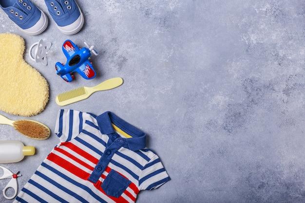 灰色の表面に小さな子供や赤ちゃん男の子のアクセサリーは、赤ちゃんの概念と旅行します。