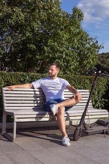 Мужчина в белой футболке сидит на скамейке со своим эскутером в парке на улице в солнечную погоду