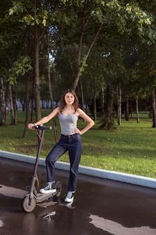 Брюнетка на экологичном электрическом самокате в парке в солнечную погоду на тротуарах