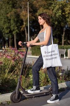 Брюнетка катается на скутере с сумкой на плече в парке в солнечную погоду с улыбкой