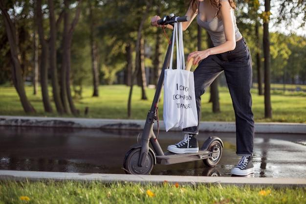 公園で電動スクーターの隣に立っているブルネットの少女は、バッグのパンから引き出します