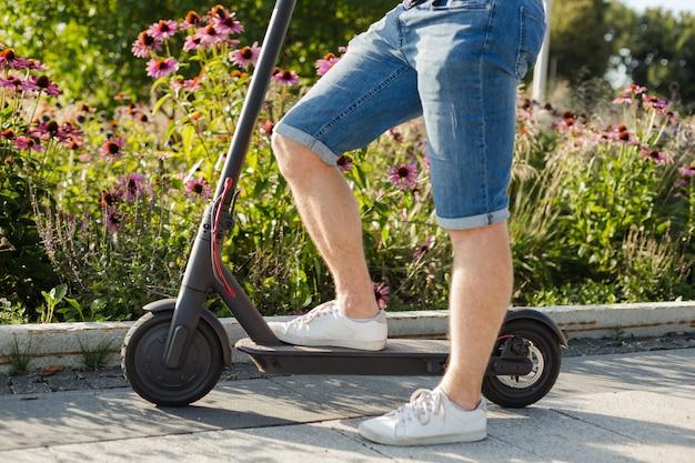 歩道の晴れた日の公園で環境に優しい電動キックスクーターに乗って男。閉じる