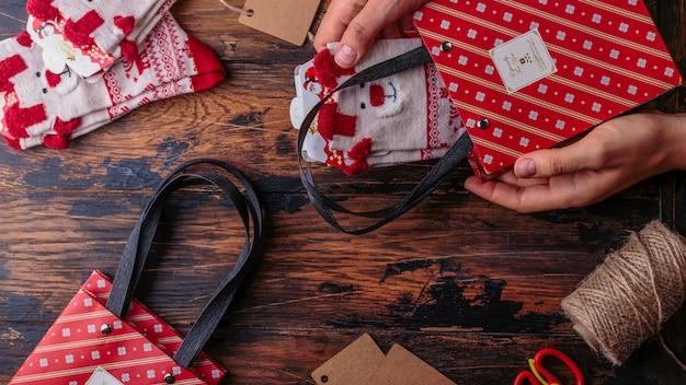 Рождественский фон взгляд сверху рук женщины оборачивает подарок нового года и смычок галстука.