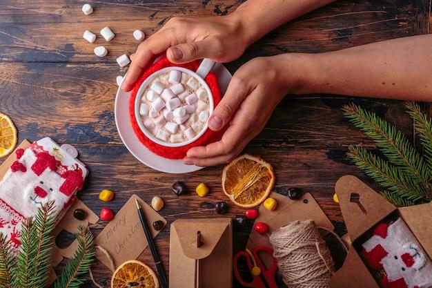女性の手はマグカップクリスマスコンセプトのマシュマロニット布でホットカカオのマグカップを取る