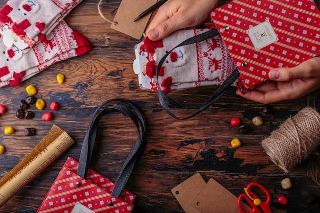 Рождественские украшения. вид сверху на руки обернуть подарком. упакованный подарок