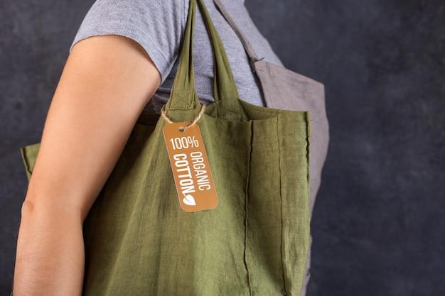Девушка в серой футболке несет на плече зеленую хлопковую сумку. изделия из органических материалов