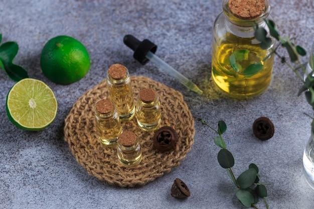 Набор стеклянных бутылок с эфирным маслом эвкалипта на серых столовых листьях в вазе