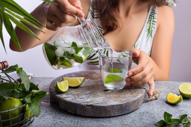 Молодая женщина наливает свежий лимонад из кувшина в стакан