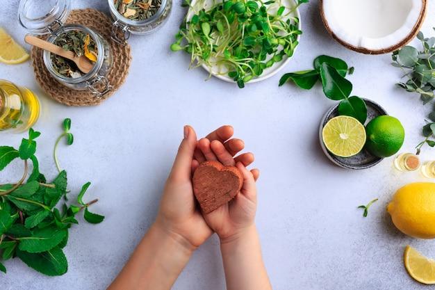 母は有機自然食品を食べて子供の手のケアの概念を保持しています。