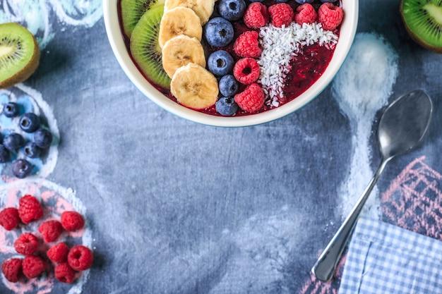 チョークボード上のボウルにおいしいアサイスムージーと健康的な朝食