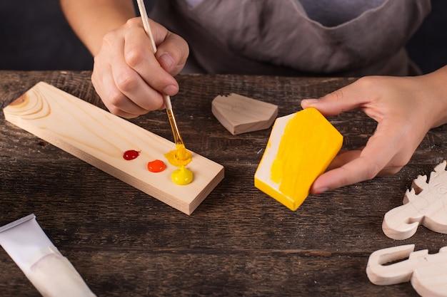 女性がワークショップでクリスマスツリーグッズを作成します。黄色の木製ブランクをペイントします。