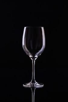 Пустой бокал для вина на черной стене