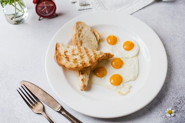 Время завтрака. два жареных яйца с тостами на завтрак с газетой и будильником