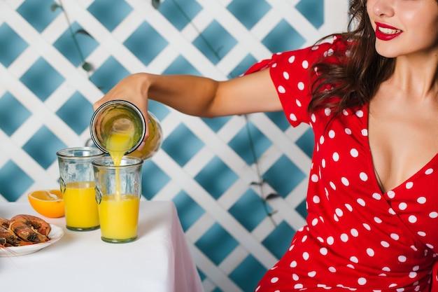Очаровательная девушка в красном платье сидит за столом и наливает сок. крупный план