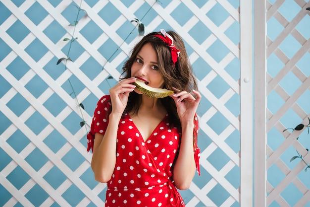Очаровательная девушка в красном платье ест дыню