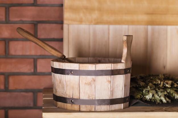 ひしゃくとサウナのほうきが付いている木製のバケツ