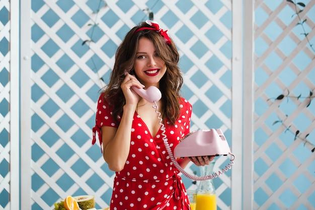 Очаровательная девушка в красном платье, разговаривает по телефону. сочные цвета