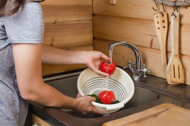 流水の下で台所で女性の手は完熟トマトを洗う