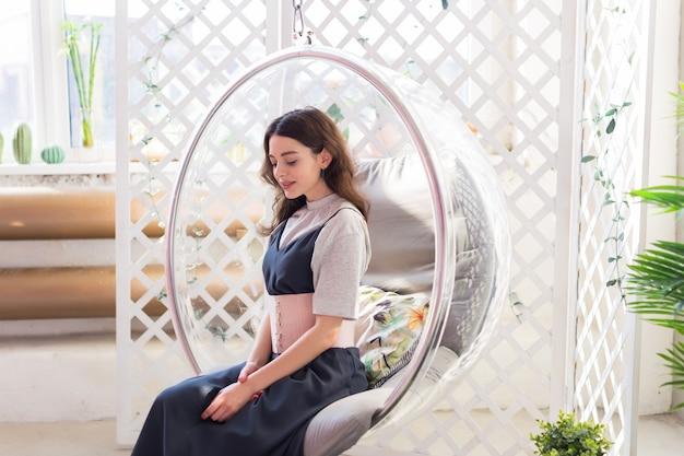 Девушка сидит в прозрачном кресле и позирует для фото