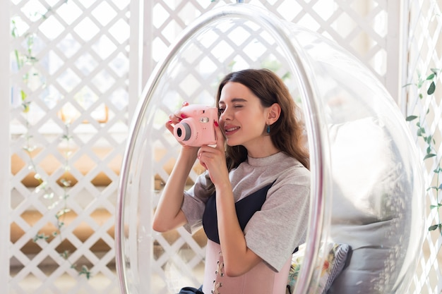 Девушка сидит в прозрачном кресле и делает фото на мгновенную камеру