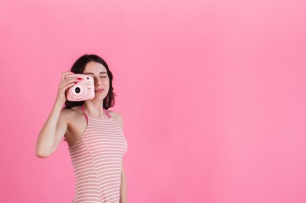 Молодая девушка в розовом полосатом платье держит камеру в руках