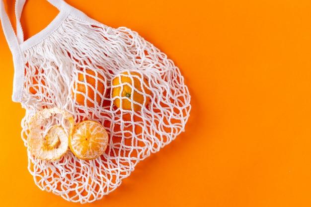 Плоские мандарины в сетчатой сумке, концепция без отходов