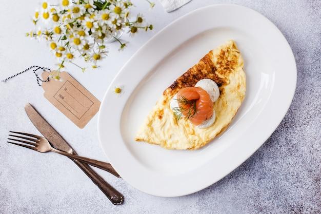 Время завтрака. омлет с красной рыбой и ромашками в вазе на светло-сером столе