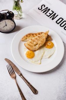 Время завтрака. два жареных яйца с тостами на завтрак на текстурированной светло-серой
