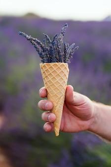 男の手にワッフルカップにラベンダーの花。
