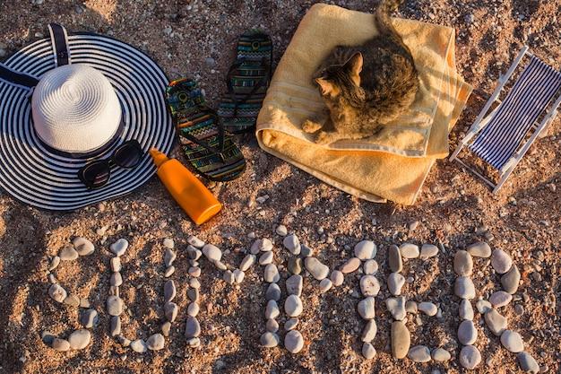Вид сверху на песчаный пляж у моря, пляжные принадлежности выложены на песке. слово лето выложено из камня