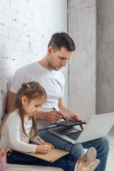 マルチタスク、フリーランス、父権のコンセプト-ホームオフィスで娘とラップトップコンピューターを持つ父親