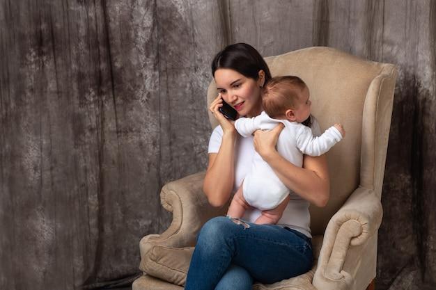 Молодая мама разговаривает по мобильному телефону с новорожденным ребенком в руках