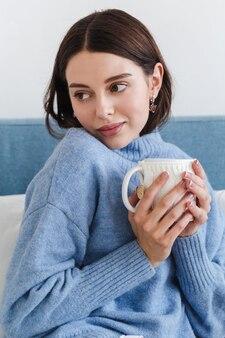女の子の美しい顔、青いセーターの少女は彼女の手で熱いお茶を一杯とソファに座っています。