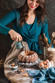 イースターケーキにアイシングを注ぐ女性の手は木の板で提供しています