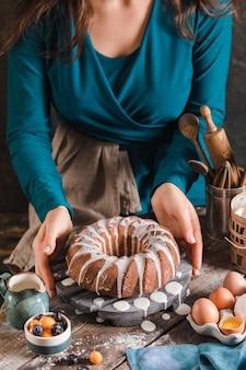 テーブルに出されるとき、女性の手で開催された木の皿にイースターイーストケーキ