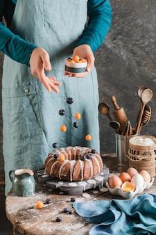 木の板にイースターイーストケーキに果実を注ぐ女性の手
