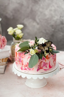 Розовый торт, украшенный цветами и настоящими бабочками, поднял романтическую атмосферу