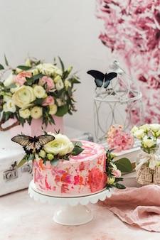 花と本物の蝶で飾られたピンクのケーキはロマンチックな雰囲気をバラ