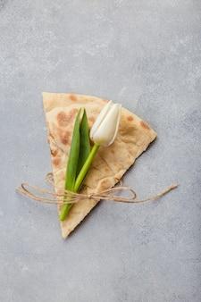 Творческий мир пиццы с цветами тюльпанов на сером