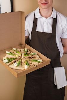 ウェイターによって提供される紙箱の花チューリップと創造的なピザ