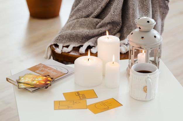 На кофейном столике лежат открытки, книга, чашка горячего чая, свечи. композиция крупным планом.