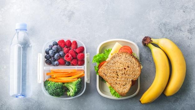Коробка школьного обеда с бананом ягод сандвича овощей на сером столе здоровой