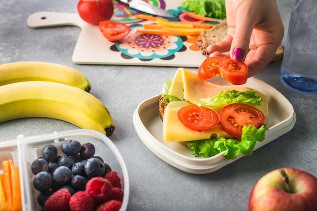 女性の手は、ランチボックスに野菜のサンドイッチを作っています。