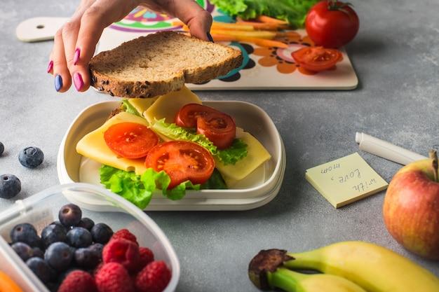 女性の手は、ランチボックスに野菜とチーズのサンドイッチを作っています。