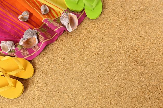 タオルとフリップフロップのビーチの背景