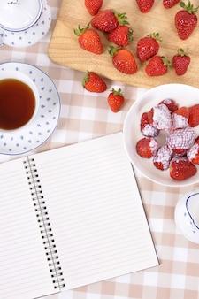 お茶といくつかのイチゴを持ちます